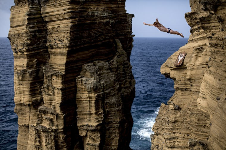 In this handout image provided by Red Bull, Andy Jones of the USA dives from 27 metres off the cliff face of Islet Vila Franca do Campo during the fifth stop of the Red Bull Cliff Diving World Series, Azores, Portugal. (Dean Treml/Red Bull via Getty Images)