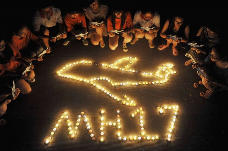 College students gather around candles forming the shape of an airplane, during a candlelight vigil for victims of the downed Malaysia Airlines Flight MH17, at a university in Yangzhou, Jiangsu province. (China Stringer Network/Reuters)