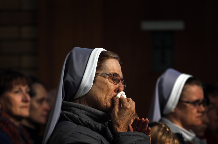 "A nun and member of the Australian Ukrainian community wipes her nose during a prayer vigil for those killed in the crash of Malaysia Airlines flight MH17, at the St Andrew's Ukrainian Catholic church in Sydney. Australian Prime Minister Tony Abbott blamed Russia on Friday for the shooting down of MH17 over eastern Ukraine, killing all 298 people on board, including 28 Australians. Abbott appeared to go further than other Western leaders in apportioning blame over the crash, demanding that Moscow answer questions about the ""Russian-backed rebels"" that he said were behind the disaster. (David Gray/Reuters)"