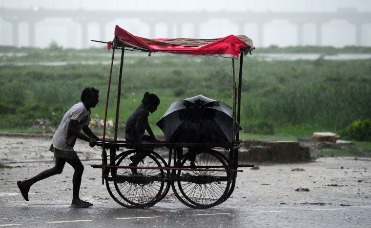 Heavy rains fall as an Indian man pushes a trolley in Allahabad. The southwest monsoon covered the entire country on July 17, two days behind the normal schedule. (Sanjay Kanojia/AFP-Getty Images)