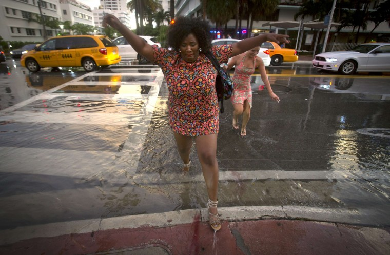 A woman jumps over a puddle as she crosses a street after a torrential downpour in the South Beach part of Miami. (Carlo Allegri/Reuters)