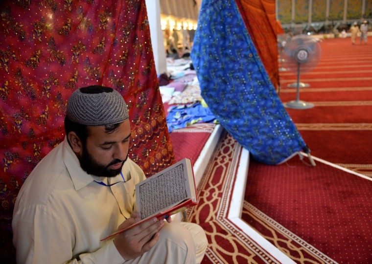 A Pakistani Muslim devotee reads the Koran as he attends Itikaf worship during the holy month of Ramadan at the Grand Faisal mosque in Islamabad. Itikaf is a spiritual retreat in a mosque, usually held during the last 10 days of Ramadan, and during which Muslims will spend the evening and night in the mosque devoting their time to solitary prayers and reading the Koran. (Aamir Qureshi/AFP-Getty Images)