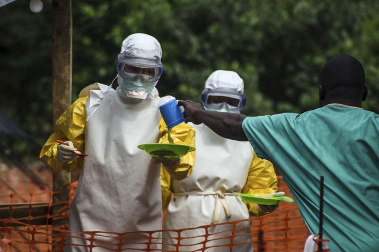 Medical staff working with Medecins sans Frontieres (MSF) prepare to bring food to patients kept in an isolation area at the MSF Ebola treatment centre in Kailahun on July 20, 2014. (REUTERS/Tommy Trenchard)
