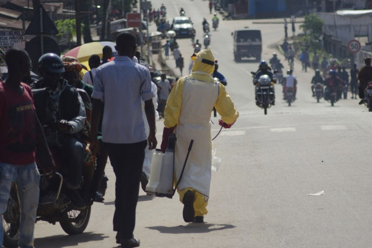 A health worker with disinfectant spray walks down a street outside the government hospital in Kenema, July 10, 2014. Ebola has killed 632 people across Guinea, Liberia and Sierra Leone since an outbreak began in February, putting strain on a string of weak health systems facing one of the world's deadliest diseases despite waves of international help. Picture taken July10, 2014. (Tommy Trenchard/Reuters)