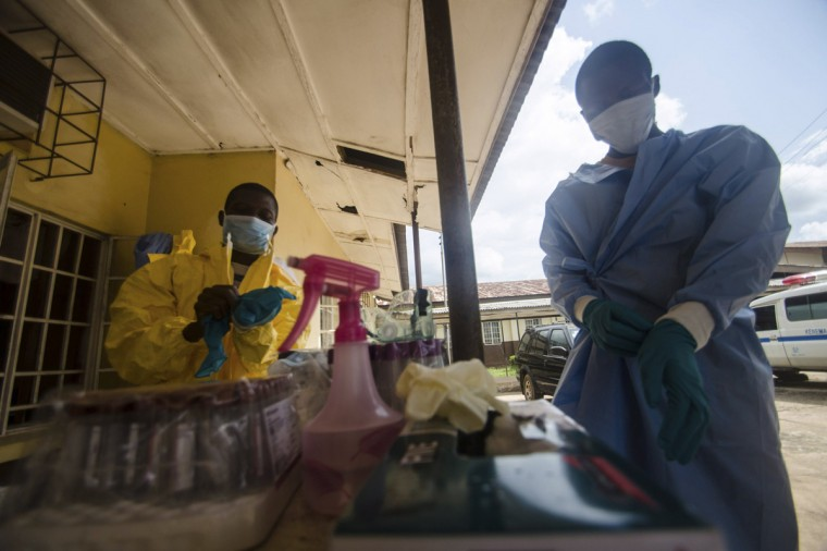 Medical staff put on protective gear in Kenema government hospital before taking a sample from a suspected Ebola patient in Kenema, July 10, 2014. Ebola has killed 632 people across Guinea, Liberia and Sierra Leone since an outbreak began in February, putting strain on a string of weak health systems facing one of the world's deadliest diseases despite waves of international help. Picture taken July10, 2014. (Tommy Trenchard/Reuters)