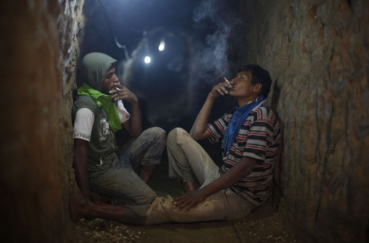 Palestinian tunnel workers smoke cigarettes as they rest inside a smuggling tunnel flooded by Egyptian security forces, beneath the Gaza-Egypt border in the southern Gaza Strip on September 10, 2013. (REUTERS/Ibraheem Abu Mustafa)
