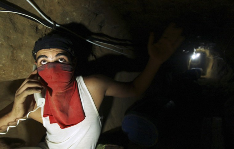 A Palestinian smuggler speaks on a phone with other smugglers in a tunnel beneath the Egyptian-Gaza border on October 21, 2008. (REUTERS/Suhaib Salem)