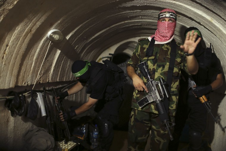 A Palestinian fighter from the Izz el-Deen al-Qassam Brigades, the armed wing of the Hamas movement, gestures inside an underground tunnel in Gaza on August 18, 2014. (REUTERS/Mohammed Salem)