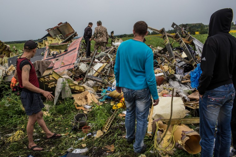 Men look at the wreckage of passenger plane Air Malaysia flight MH17 on July 18, 2014 in Grabovka, Ukraine. Air Malaysia flight MH17 travelling from Amsterdam to Kuala Lumpur crashed yesterday on the Ukraine/Russia border near the town of Shaktersk. The Boeing 777 was carrying 298 people including crew members, the majority of the passengers being Dutch nationals, believed to be at least 173, 44 Malaysians, 27 Australians, 12 Indonesians and 9 Britons. It has been speculated that the passenger aircraft was shot down by a surface to air missile by warring factions in the region. (Photo by Brendan Hoffman/Getty Images)