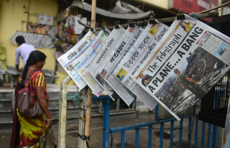 An Indian pedestrian walks past newspapers featuring the crash of a Malaysia Airlines plane carrying 298 people from Amsterdam to Kuala Lumpur at a newspaper stand in Siliguri on July 18,2014. Pro-Russian separatists in the region and officials in Kiev blamed each other for the crash, after the plane was apparently hit by a surface-to-air missile. All 298 people on board Flight MH17 died when the plane crashed. (Duptendu DUtta/AFP/Getty Images)