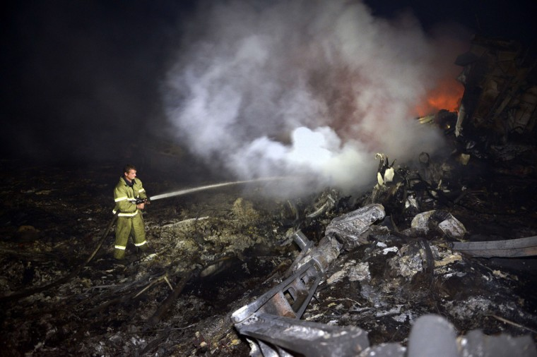 "A firefighter sprays water to extinguish a fire, on July 17, 2014, amongst the wreckages of the malaysian airliner carrying 295 people from Amsterdam to Kuala Lumpur after it crashed, near the town of Shaktarsk, in rebel-held east Ukraine. Ukrainian President Petro Poroshenko said on Thursday that the Malaysia Airlines jet that crashed over rebel-held eastern Ukraine may have been shot down.""We do not exclude that the plane was shot down and confirm that the Ukraine Armed Forces did not fire at any targets in the sky,"" Poroshenko said in a statement posted on the president's website. (Alexander Khudoteply/AFP/Getty Images)"