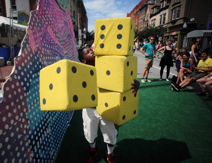 Anthony Fuller, 11, stacks oversized dice as he prepares to make a big roll playing Farkle, a dice game where the player tries to reach a certain dice combination marking a point value. He was plating the game on Charles Street at Artscape 2014. (Al Drago/Baltimore Sun)
