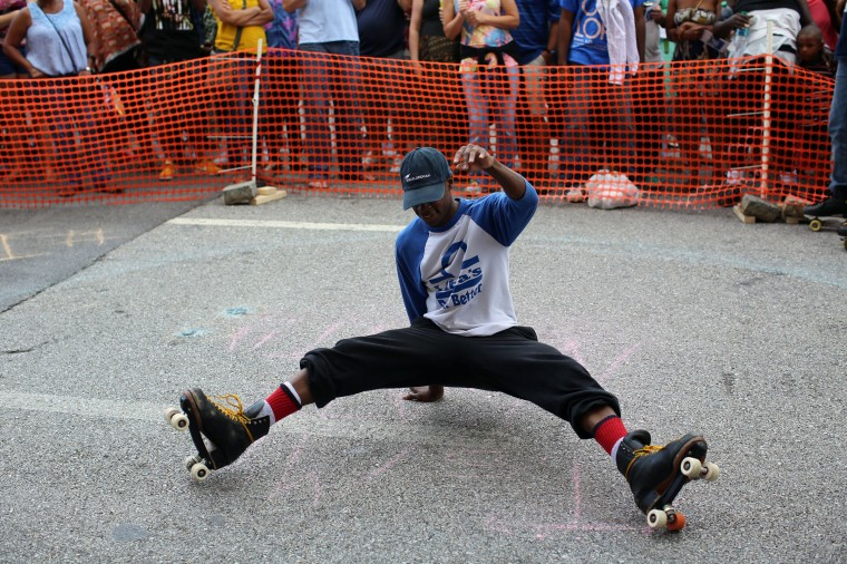 """Skater Mark Bank, also known as """"Swizzy,"""" jumps back onto his skates while performing with It's My Skate Night at Artscape 2014. (Al Drago/Baltimore Sun)"""