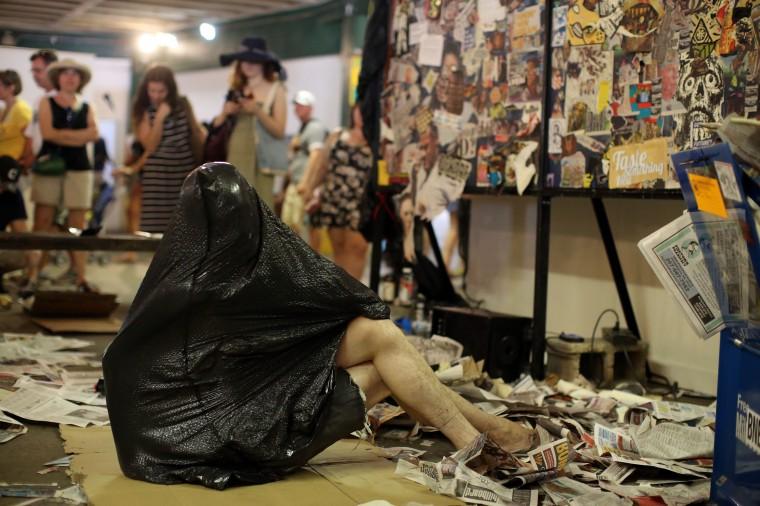 A plastic bag is part of the art as Rev. Eric Dangerdark does trash yoga while creating the Philadelphia Septa System with the Philadelphia artist-run collective Little Berlin at Artscape 2014. (Al Drago/Baltimore Sun)