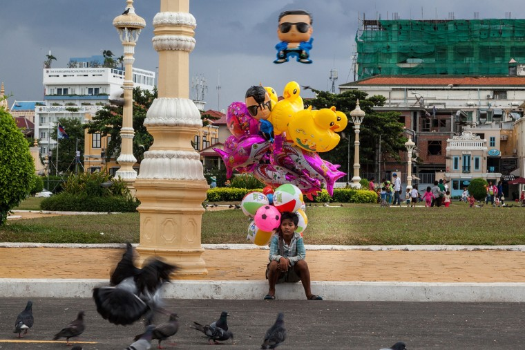 An underage balloon seller sits watching pigeons in front of the Royal Palace in Phnom Penh, Cambodia. After months of negotiations Australia and Cambodia look set to agree on a deal which will see 1000 refugees transferred from Australia to Cambodia. The discussions have been met with intense opposition as people fear the deal could overwhelm Cambodia's refugee infrastructure. In return for almost emptying Australia's Nauru Island detention center, it has been reported that Australia will pay the Cambodian government $40 million. (Omar Havana/Getty Images)