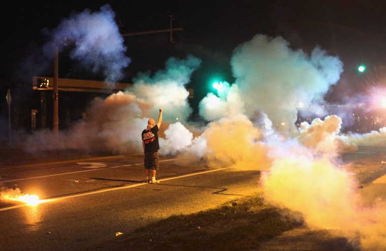 A demonstrator, protesting the shooting death of teenager Michael Brown, stands his ground as police fire tear gas on August 13, 2014 in Ferguson, Missouri. Brown was shot and killed by a Ferguson police officer on Saturday. Ferguson, a St. Louis suburb, is experiencing its fourth day of violent protests since the killing. (Photo by Scott Olson/Getty Images)