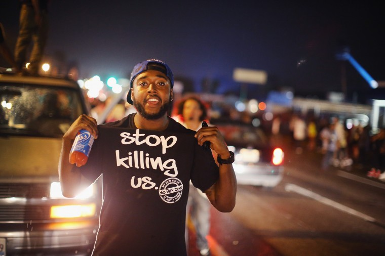 Demonstrators gather along West Florissant Avenue to protest the shooting of Michael Brown on August 15, 2014 in Ferguson, Missouri. Brown was shot and killed by a Ferguson police officer on August 9. Tonight's demonstration again ended with protestors clashing with police followed by more looting. (Photo by Scott Olson/Getty Images)