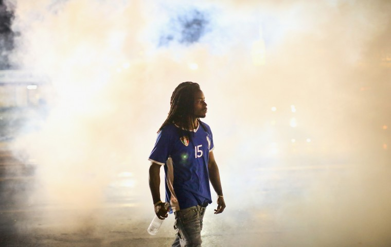 A demonstrator walks through smoke launched by police after a skirmish on August 15, 2014 in Ferguson, Missouri. Police sprayed pepper spray, shot smoke, gas and flash grenades at protestors before retreating. Several businesses were looted following the skirmish as police held their position nearby. Violent outbreaks have taken place in Ferguson since the shooting death of Michael Brown by a Ferguson police officer on August 9. (Photo by Scott Olson/Getty Images)