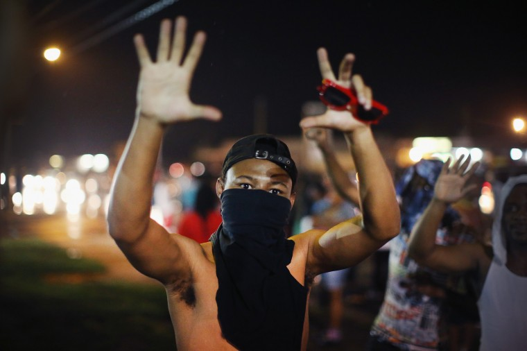 A demonstrator confronts police during a protest over the shooting of Michael Williams on August 15, 2014 in Ferguson, Missouri. Police sprayed pepper spray, shot smoke, gas and flash grenades at protestors before retreating. Several businesses were looted following the skirmish as police held their position nearby. Violent outbreaks have taken place in Ferguson since the shooting death of Brown by a Ferguson police officer on August 9. (Photo by Scott Olson/Getty Images)