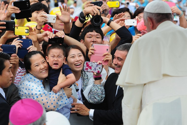 In this handout image provided by the Committee for the 2014 Papal Visit to Korea, The faithful greet Pope Francis upon his arrival for the 6th Asian Youth Day on August 17, 2014 in Haemi, South Korea. Pope Francis is visiting South Korea from August 14 to August 18. This trip is the third trip abroad for the pope following Brazil and the Middle East. This is the third pontifical visit to South Korea. (Photo by Committee for the 2014 Papal Visit to Korea via Getty Images)
