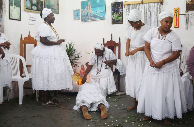 A worshipper lies on the floor after falling into a trance during a Candomble ceremony on August 17, 2014 in Cachoeira, Brazil. Candomble is an Afro-Brazilian religion whose practitioners often fall into trances during ceremonies and believe they have become possessed by gods, or orixas. The roots of the religion came to Brazil via African slaves while eventually incorporating elements of Catholicism. The state of Bahia received at least 1.2 million slaves from Africa and remains the most African of Brazilian states, where blacks make up around 80 percent of the population. (Photo by Mario Tama/Getty Images)