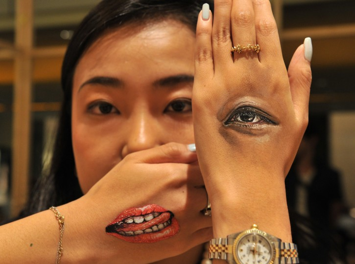 "A woman displays body-paintings of her eye and her mouth on the back of her hands after Japanese body-painting artist Hikaru Cho (unseen in this picture) painted at an art event called ""Future en-nichi"" in Tokyo on August 6, 2014. En-nichi is a popular Japanese summer festival and 12 contemporary artists exhibit through to August 10. (Yoshikazu Tsuno/Getty Images )"