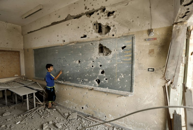 A Palestinian boy writes on a shrapnel riddled backboard at the heavily damaged Sobhi Abu Karsh school in Gaza City's al-Shejaea neighborhood on August 5, 2014, as a 72-hour humanitarian truce went into effect in the Gaza Strip after a month of fighting between Hamas and Israeli forces. Hamas may have hemorrhaged rockets and fighters, but its latest war with Israel has boosted its popularity in the Gaza Strip even if long-term gains look remote, analysts say. (Mohammed Abed/Getty Images)