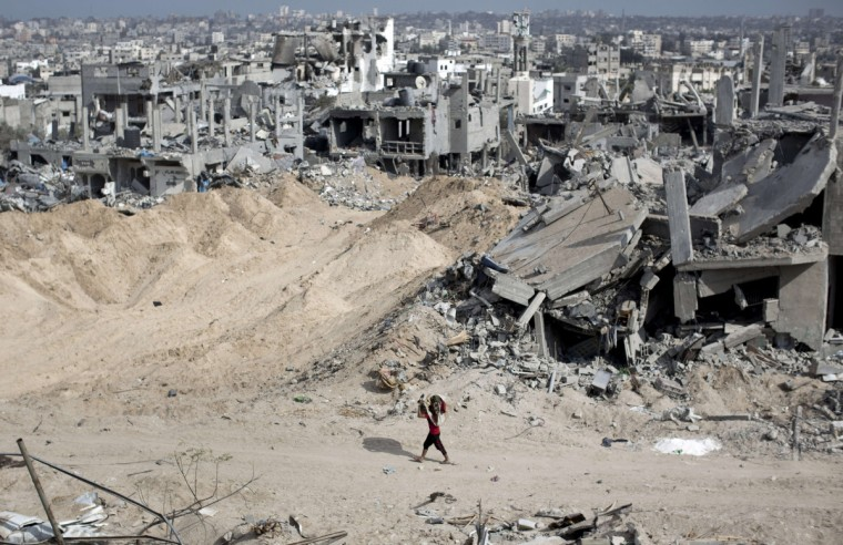 A Palestinian youth carries items salvaged from the rubble past destroyed buildings in part of Gaza City's al-Tufah neighborhood as the fragile ceasefire in the Gaza Strip entered a second day on August 6, 2014 while Israeli and Palestinian delegations prepared for crunch talks in Cairo to try to extend the 72-hour truce. The ceasefire, which came into effect on August 5, has brought relief to both sides after one month of fighting killed 1,875 Palestinians and 67 people on the Israeli side. (Mahmud Hams/Getty Images)