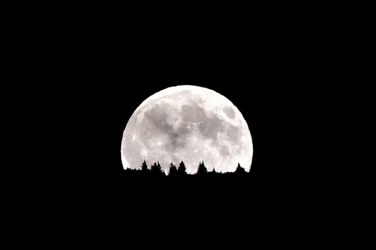 """The full moon nicknamed """"the supermoon"""", rises over the Dolomiti mountains in Levico Terme near Trento in north of Italy on August 10, 2014. A supermoon is the coincidence of a full moon or a new moon with the closest approach the Moon makes to the Earth on its elliptical orbit, resulting in the largest apparent size of the lunar disk as seen from Earth. (Giuseppe Cacace/Getty Images)"""