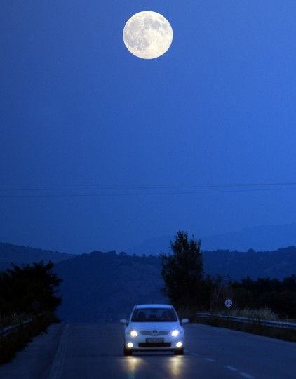 """The full moon, nicknamed """"the supermoon"""", rises over road near the town of Bitola on August 10, 2014. A supermoon is the coincidence of a full moon or a new moon with the closest approach the Moon makes to the Earth on its elliptical orbit, resulting in the largest apparent size of the lunar disk as seen from Earth. (Robert Atanasovski/Getty Images)"""