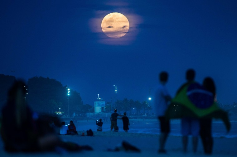 """The full moon, nicknamed """"the supermoon"""", rises at Ipanema beach in Rio de Janeiro, Brazil, on August 10, 2014. A supermoon is the coincidence of a full moon or a new moon with the closest approach the Moon makes to the Earth on its elliptical orbit, resulting in the largest apparent size of the lunar disk as seen from Earth. (Yasuyoshi Chiba/Getty Images)"""