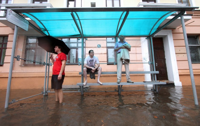 People wait for the bus in a flooded bus stop during heavy rain in Minsk. (Sergei Gapon/Getty Images)