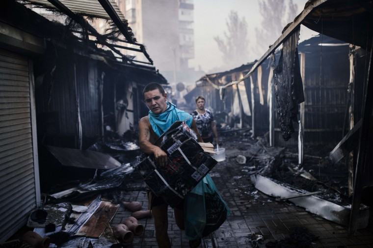 A man carries goods out of his burned shop after shelling in the town of Yasynuvata near the rebel stronghold of Donetsk . (Dimitar Dilkoff/Getty Images)