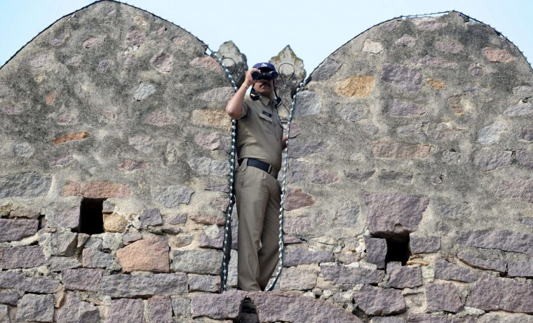 An Indian policeman looks on as colleagues from the recently formed southern Indian state of Telangana take part in a full dress rehearsal for the 68th Independence day celebrations at Golkonda Fort in Hyderabad. India celebrates its anniversary of Independence from Britain each August 15 with great pomp and ceremony. (Noah Seelam/Getty Images)
