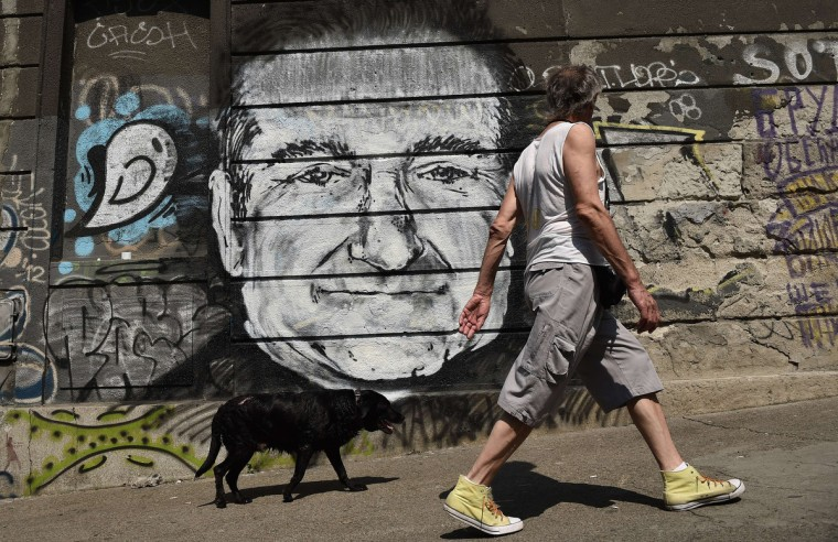 A man with his dog walk past a mural depicting actor Robin Williams in downtown Belgrade. Unknown artists drew the Academy Award-winning actor and comedian below a Belgrade bridge to pay a tribute following the news that he had been found dead of an apparent suicide at the age of 63. (Andrej Isakovic/Getty Images)