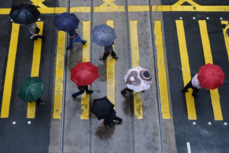 People shield themselves from the rain with umbrellas as they cross an intersection in Hong Kong. An active southwesterly airstream associated with a trough of low pressure is bringing thundery showers to the south China coast, the Hong Kong weather observatory reported. (Dale de la Rey/Getty Images)