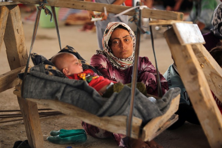 An Iraqi Yazidi woman, who fled her home when Islamic State (IS) militants attacked the town of Sinjar, looks at her baby as they rest inside a building under construction where they found refuge on the outskirts of the Kurdish city of Dohuk, in Iraq's autonomous Kurdistan region, on August 16, 2014. According to the human rights non-governmental organisation Amnesty International some 200,000 people have escaped to safety in Iraq's Kurdish region. (Ahmad al-Rubaye/AFP Getty)