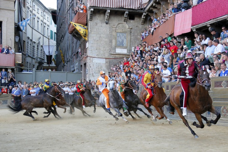 """Jockey of the Contrada of Owl, Andrea Mari (R) and others compete during the """"Palio"""" horse race on August 16, 2014 in Siena. The Palio medieval race is held twice a year in Siena with jockeys riding bareback around a makeshift race course set up in the city's central square. (Fabio Muzzi/AFP Getty)"""
