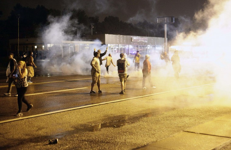 Demonstrators protesting the August 9 police shooting of 18-year-old Michael Brown react as police fire tear gas on the streets of Ferguson, Missouri early on August 17, 2014. A crowd of some 200 demonstrators defied a curfew that came into effect in Ferguson early on August 17, days after police shot dead the unarmed black teen, triggering a wave of rioting. (Joshua Lott/AFP Getty)