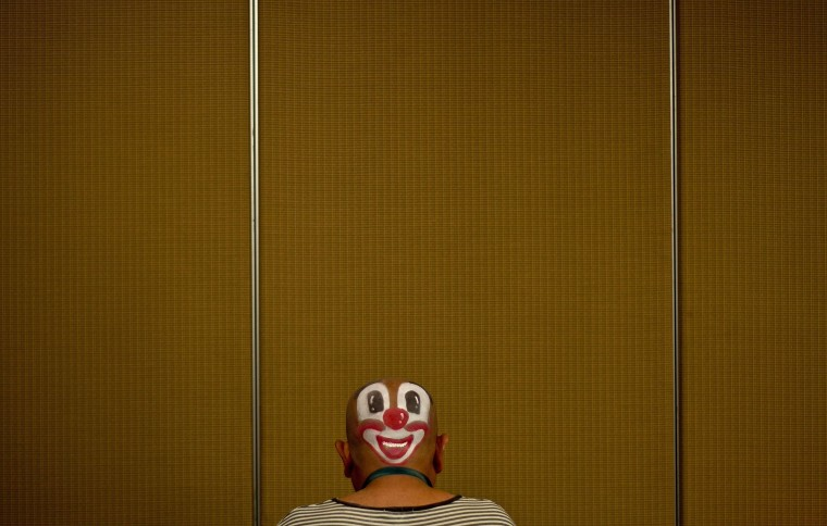 A clown prepares to take part in a Clown Festival in Kuala Lumpur on August 17, 2014. Around 80 clowns from all over Malaysia took part in the event organised by the Association of Clowns Malaysia to provide a platform for clown education, acquiring new skills and offering members support. (Manan Vatsyayana/AFP Getty)