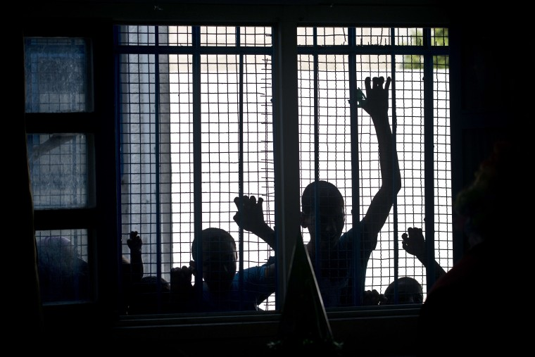 Palestinian children, who were displaced from their homes by fighting between Hamas and Israel, look through a window into a classroom where other displaced children were celebrating some of their birthdays at a UN school in Jabalia in the northern Gaza Strip, on August 17, 2014. Israel warned it would not countenance any long-term truce deal that did not answer its security needs as Gaza ceasefire talks resumed in Cairo. (Roberto Schmidt/AFP Getty)