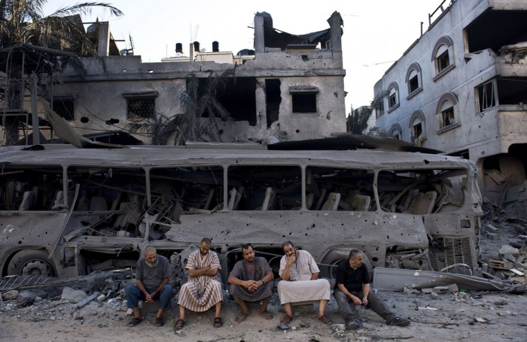 Five Palestinian men sit next to a destroyed bus and houses in front of a house that was completely demolished after it was targeted by Israeli airstrikes late on August 19. Hamas said on August 20 that an Israeli air strike killed the wife and child of its Gaza military chief, as a temporary ceasefire went up in smoke and Cairo truce talks froze. (Roberto Schmidt/Getty Images)