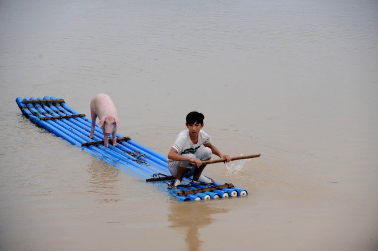 A victim makes his way through flood water on a makeshift raft in Lishui, east China's Zhejiang province after days of heavy rainfall. More than 20,000 residents have been evacuated due to the flood as the water level in Ou river keeps rising during the storms, local media reported. (Getty Images)