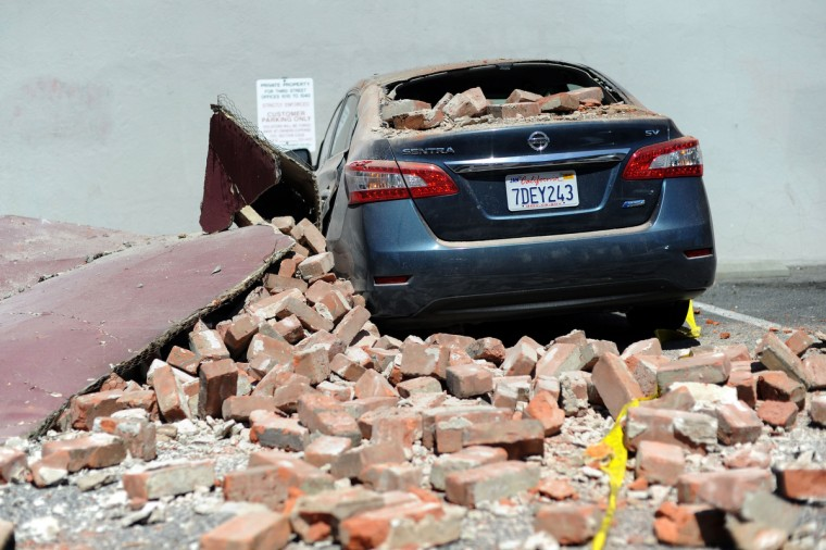 A car damaged by falling bricks is seen in downtown Napa, California after earthquake struck the area in the early hours of August 24, 2014. California's governor Jerry Brown declared a state of emergency Sunday following a strong 6.0-magnitude earthquake that seriously injured three people including a child and ignited fires in the scenic Napa valley wine region. The US Geological Service said that the quake was the most powerful to hit the San Francisco Bay area since the 1989 6.9-magnitude Loma Prieta earthquake. (Josh Edelson/Getty Images)