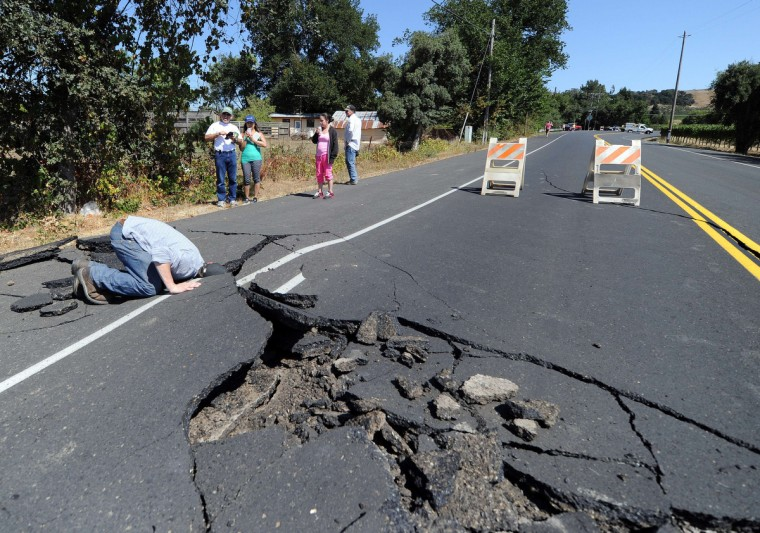 Nicholas George looks under a buckled highway just outside of Napa, California after earthquake struck the area in the early hours of August 24, 2014. California's governor Jerry Brown declared a state of emergency Sunday following a strong 6.0-magnitude earthquake that seriously injured three people including a child and ignited fires in the scenic Napa valley wine region. The US Geological Service said that the quake was the most powerful to hit the San Francisco Bay area since the 1989 6.9-magnitude Loma Prieta earthquake. (Josh Edelson/Getty Images)