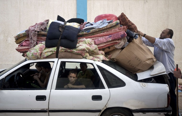 A Palestinian man straps his belongings to the roof of his car as he and his family prepare to return home from the UN school in Gaza City, following the long-term truce agreed between Israel and the Palestinians. After seven weeks of the deadliest Israeli-Palestinian violence in a decade, a long-term ceasefire took hold at 1600 GMT on August 26, sparking festivities around the Gaza Strip. (Mahmud Hams/Getty Images)
