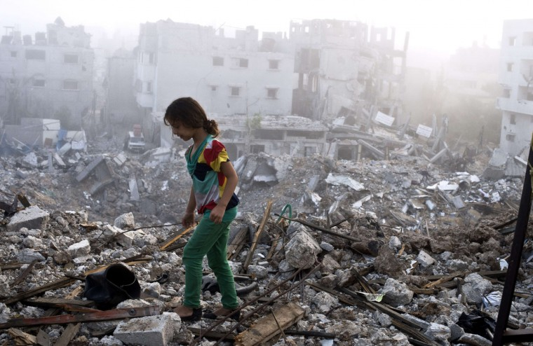 A Palestinian girl walks on the rubble strewn ceiling of her family's home after she and other members of her family returned to their partially destroyed house early in Gaza City's Shejaiya neighbourhood which was one of the hardest hit by the fighting. The skies over the Gaza Strip were calm as a long-term ceasefire between Israel and the Palestinians took hold after 50 days of the deadliest violence in a decade. (Roberto Schmidt/Getty Images)