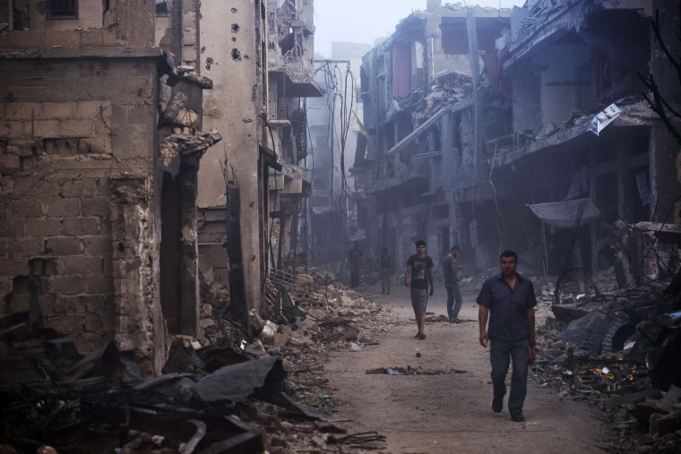 Palestinian men walk in a street among houses destroyed in Gaza City's Shejaiya neighbourhood, which was one of the hardest hit hit by the fighting between Israel and Hamas militants. The skies over the Gaza Strip were calm as a long-term ceasefire between Israel and the Palestinians took hold after 50 days of the deadliest violence in a decade. (Roberto Schmidt/Getty Images)