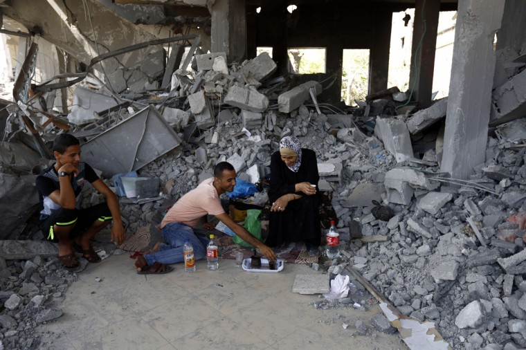 A Palestinian family drinks coffee amidst the rubble of their destroyed home upon their return in the northern Gaza Strip city of Beit Hanun. The skies over Gaza remained calm as a long-term ceasefire took hold, ending the deadliest violence in a decade with Israel and Hamas both claiming 'victory' in the 50-day war. (Mohammed Abed/Getty Images)