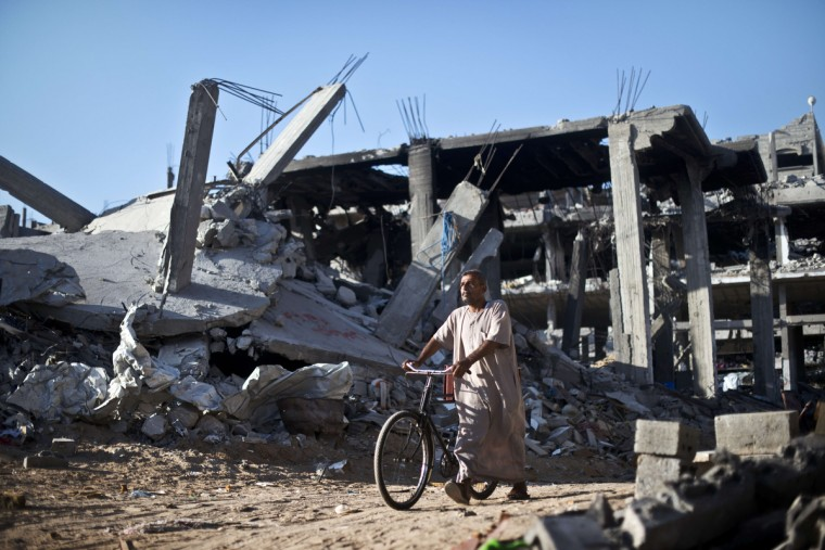 A Palestinian man pushes a bicycle past the rubble of destroyed buildings in Shejaiya. The residents of the Shejaiya neighborhood had all but emptied their neighborhood to stay with friends or with family elsewhere as they fled the fighting between Israel and Hamas militants. The skies over Gaza remained calm as a long-term ceasefire took hold, ending the deadliest violence in a decade with Israel and Hamas both claiming 'victory' in the 50-day war. (Roberto Schmidt/Getty Images)